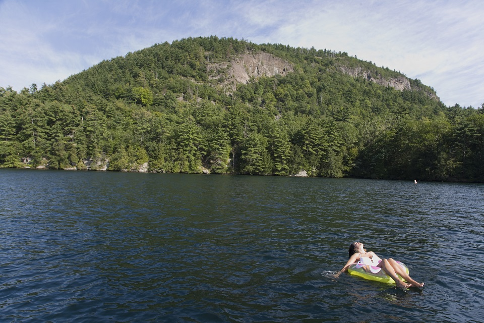 Woman floating on a tube in a Lake George Bay with a mountain in the background