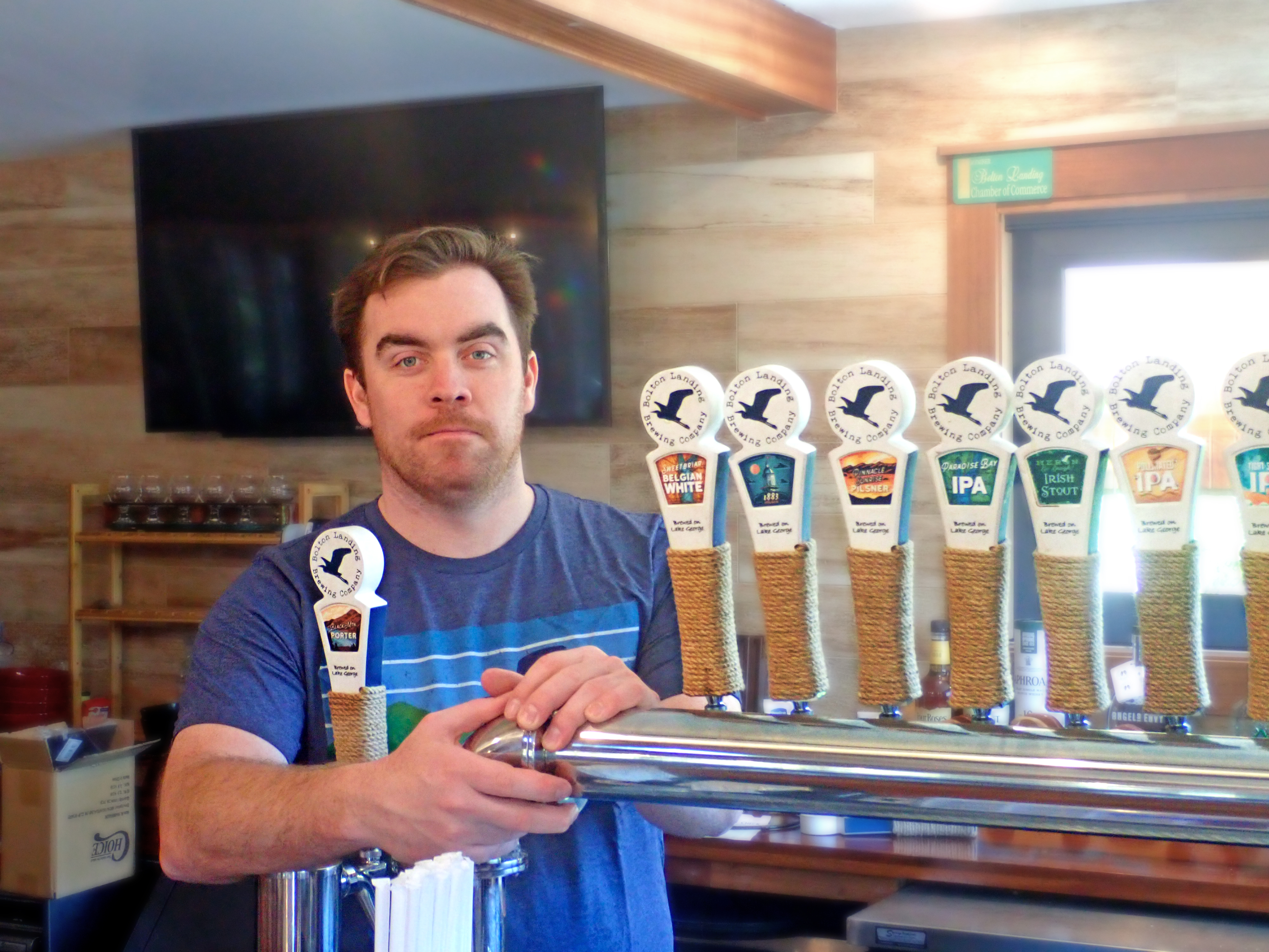 Brendan Murnane behind beer taps at the Bolton Landing Brewing Company