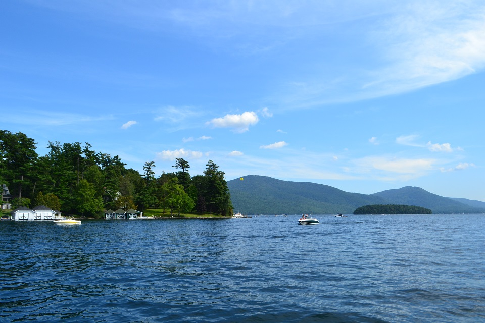 Boats on Lake George with the Adirondack Mountains in the background and camps on the shoreline