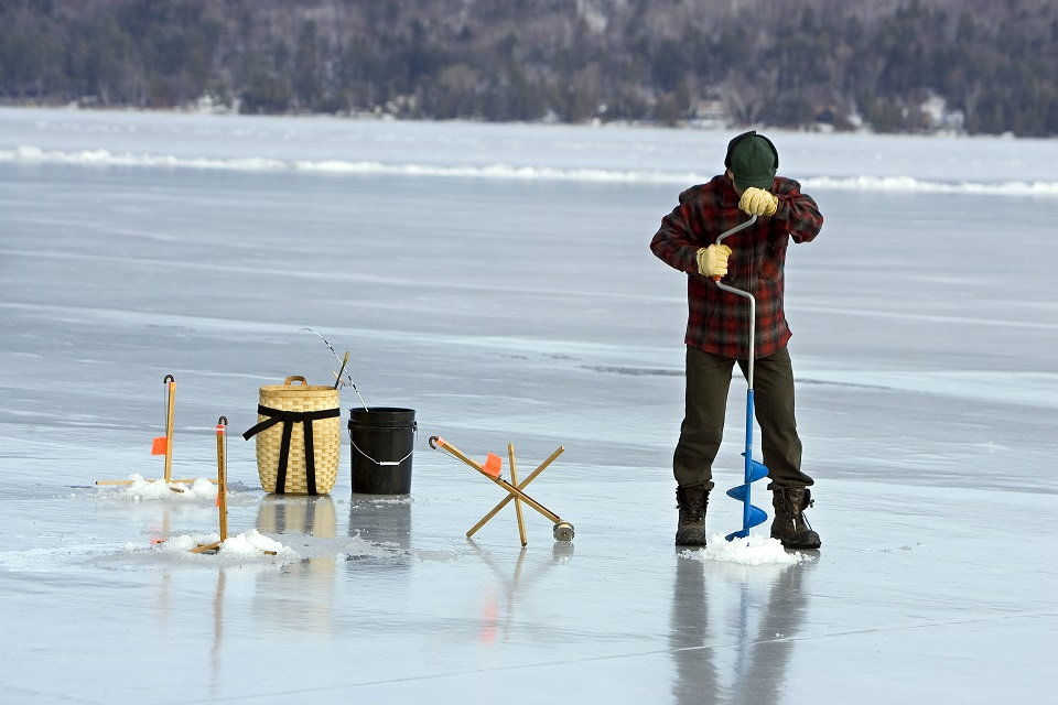 Ice Fisherman drilling a hole in the ice for ice fishing