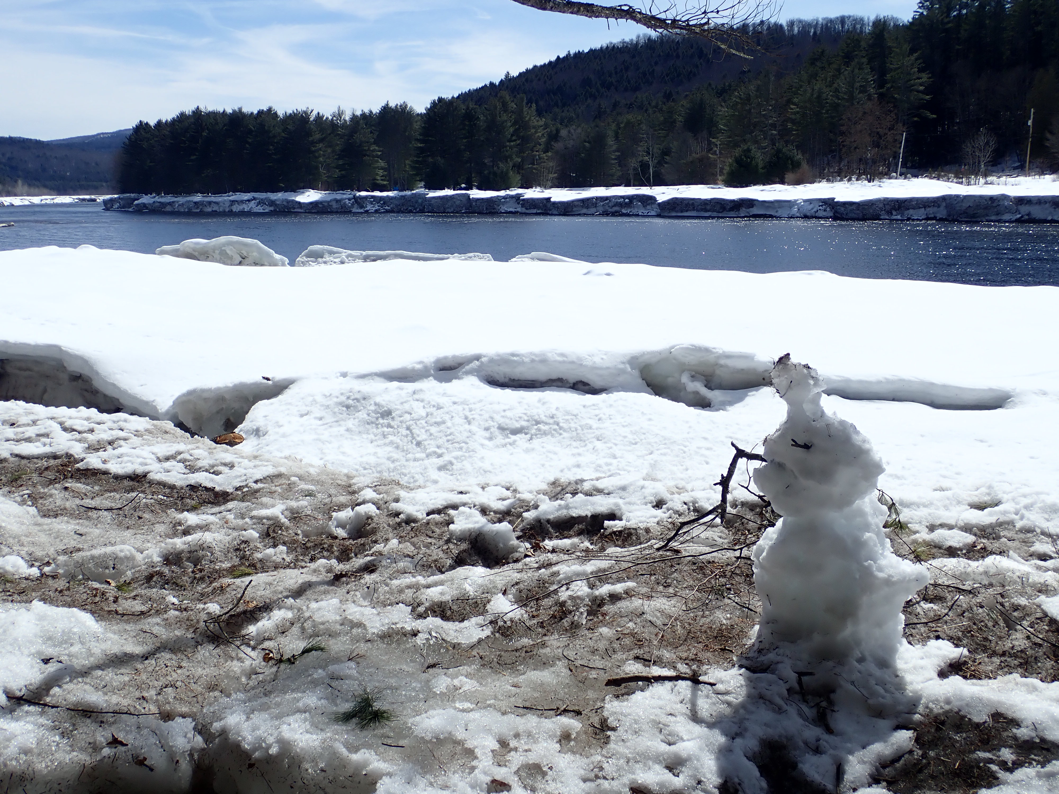 a melting snowman on the Warren County Nature Trails with the Hudson River in the background