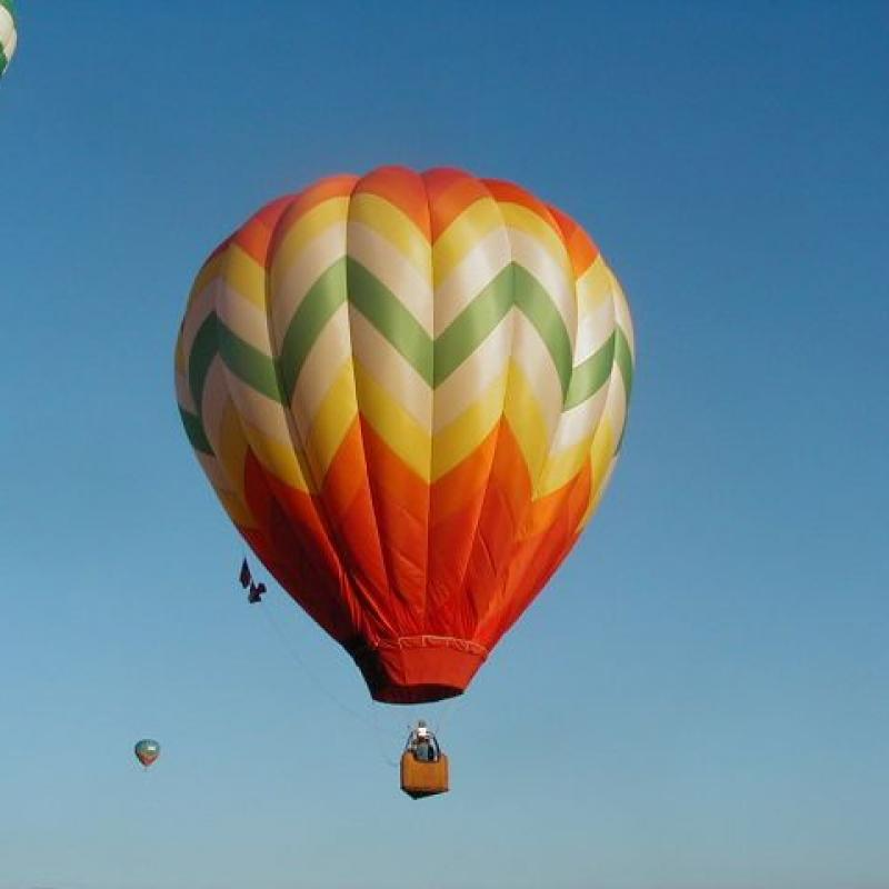 A red, orange, yellow, white, and green zig zag patterned hot air balloon