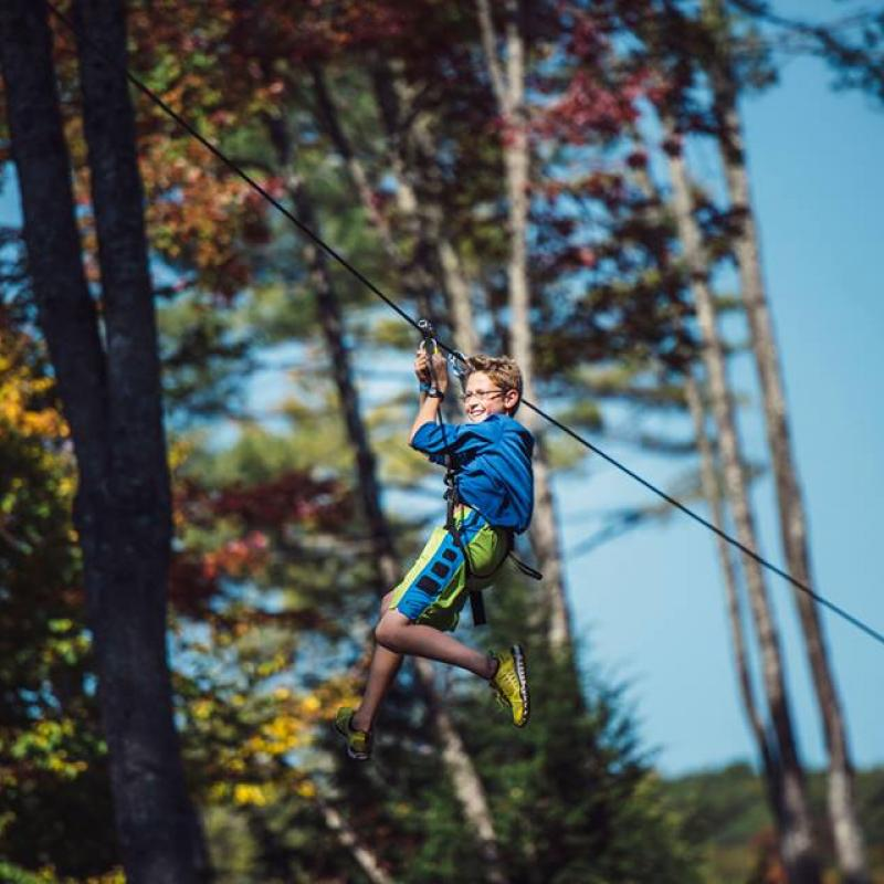 Boy zip lining at Adirondack Extreme Adventure Course