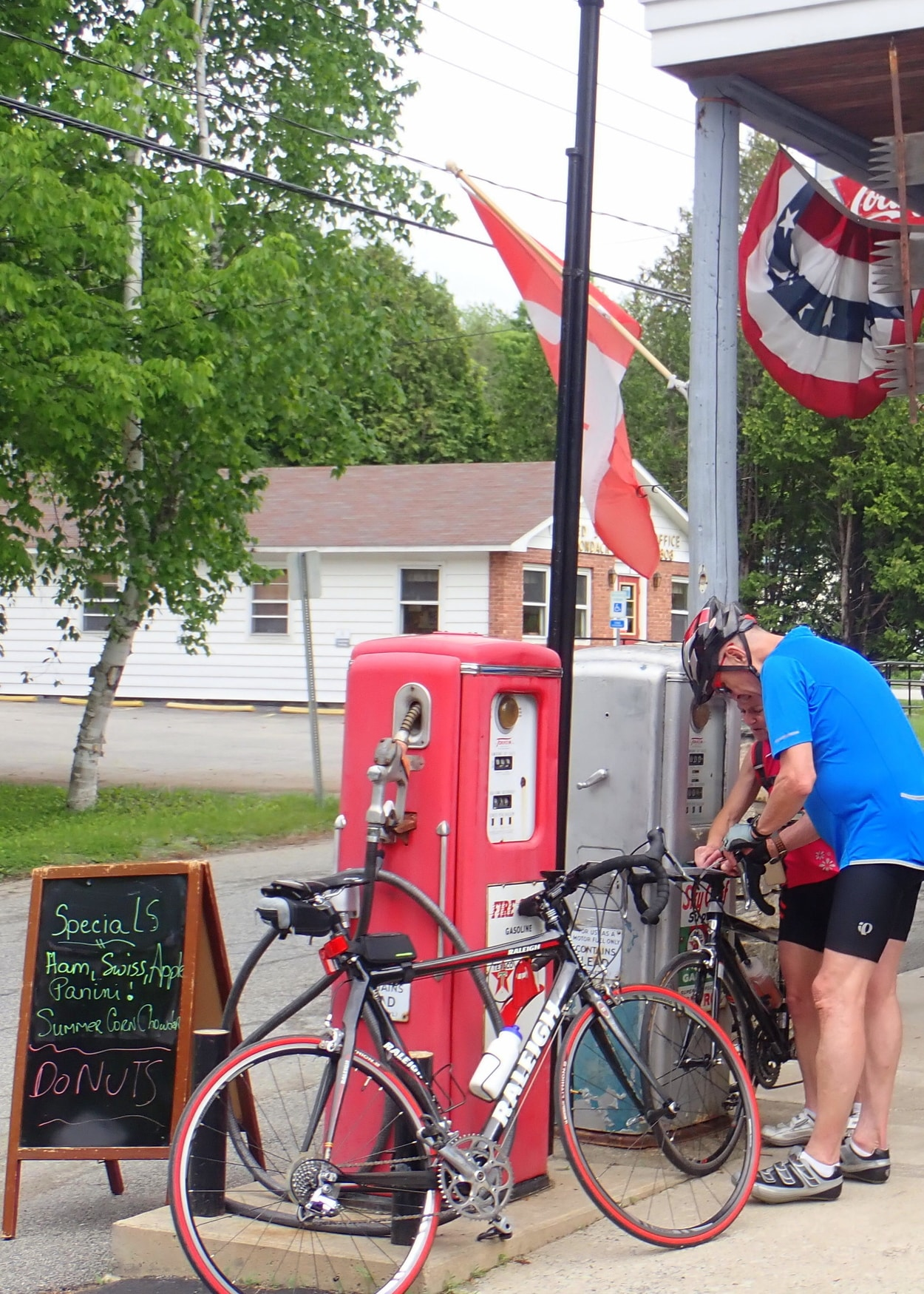 man with his bike next to the gas pumps at the Adirondack General Store in Schroon Lake