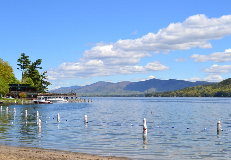 Shepard Park beach with buoys and Adirondack Mountains in the background